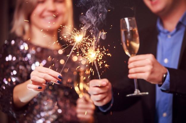 黒の背景にシャンパングラスと線香花火とカップルの写真