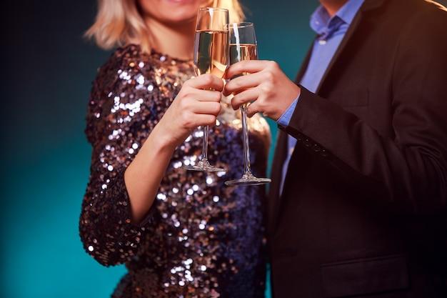黒の背景にシャンパンとシャンパングラスとカップルの写真