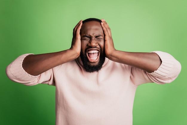 Фото сумасшедшего раздраженного избегающего человека прикрывают уши криком в белой рубашке на зеленом фоне