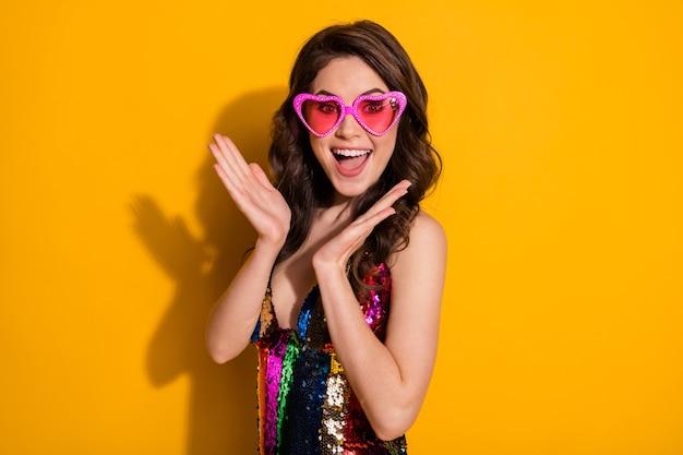 Фотография безумно удивленной мечтательной очаровательной девушки впечатлила невероятными скидками на распродажах в юбке, изолированной на ярком блестящем цветном фоне
