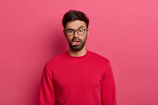 미친 수염 난 남자의 사진은 혀를 내밀고, 눈을 교차하고, 피곤하고 지루하며, 안경과 빨간 스웨터를 입고, 어리석은 짓을하고, 분홍색 벽에 포즈를 취합니다. 만화 얼굴 표정 개념