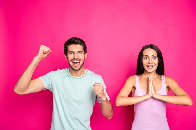 Фотография сумасшедшей пары, парня и леди, поднимающих кулаки, хотят, чтобы футбольная команда выиграла матч, соревнования, носить повседневную одежду, изолированную ярким розовым цветом фона
