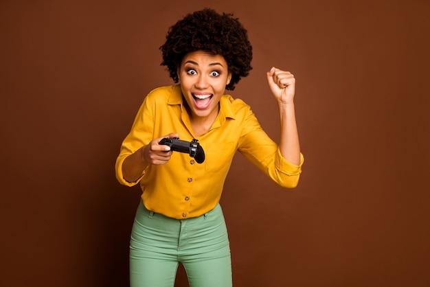 Фото сумасшедшей смешной темнокожей кудрявой дамы, держащей джойстик, играющей наркоман к видеоиграм, лидер онлайн-команды геймера, одетый в желтую рубашку, зеленые штаны, изолированный коричневый цвет