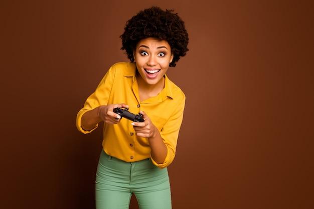 Фото сумасшедшей смешной темнокожей волнистой дамы, держащей джойстик, играющей наркоман к видеоиграм, лидер онлайн-команды геймера, одетый в желтую рубашку, зеленые брюки, изолированный коричневый цвет