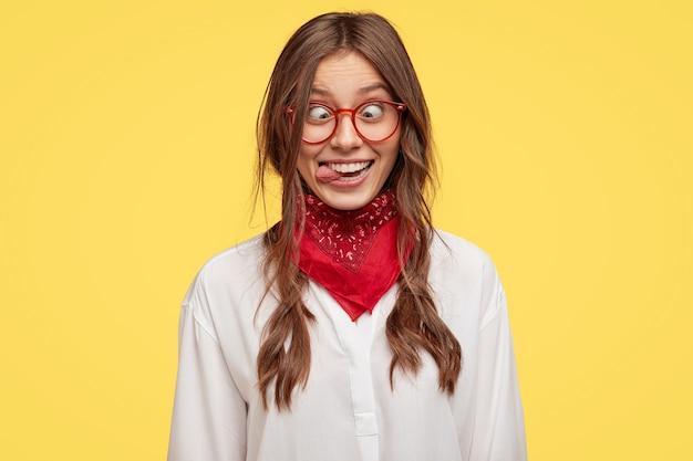 미친 여자 친구의 사진은 재미있는 얼굴을 만들고, 눈을 교차하고, 혀를 내밀고, 바보를 연기합니다.