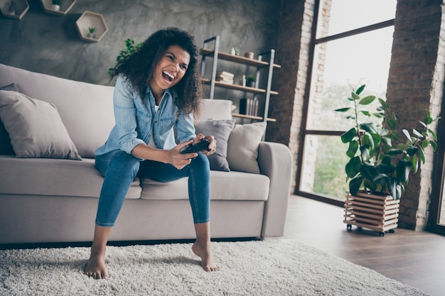 Фотография сумасшедшей красивой темной кожи, волнистой, забавной леди, держащей джойстик консоли геймпада, увлеченного геймера, взволнованного победой, сидя на уютном диване, в повседневной джинсовой одежде, в гостиной в помещении