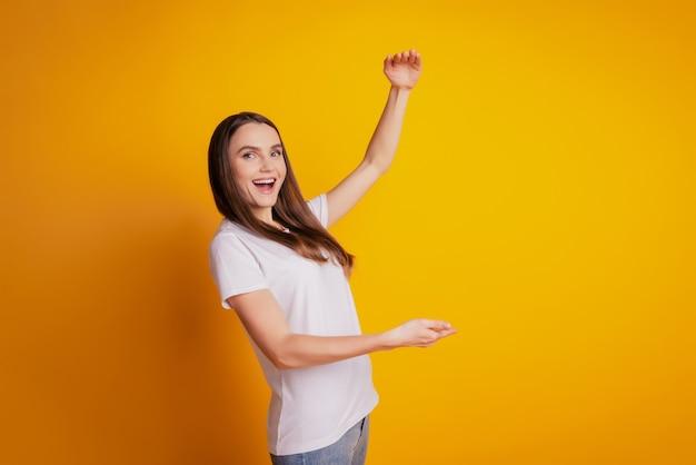 Фото сумасшедшего промоутера леди руки измеряют размер пустого пространства в белой футболке позирует на желтом фоне
