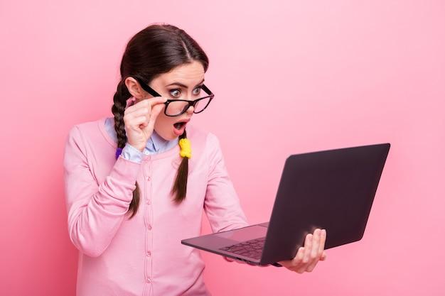 クレイジーショックを受けた学生の女性の写真は、コンピューターのノートブックの手を握り、メールの先生のインターネットを読む大きな宿題を着るシャツのプルオーバーの仕様は、パステルピンク色の背景を分離しました