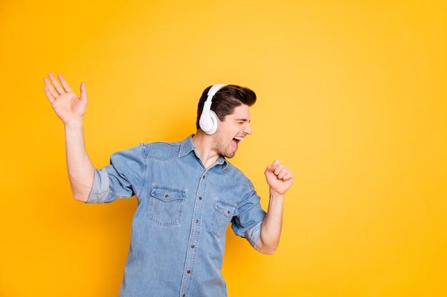 鮮やかな色の壁に隔離されたリスニングのためにワイヤレスヘッドフォンを使用して架空のマイクに向かって叫んでいる狂った歌手の写真