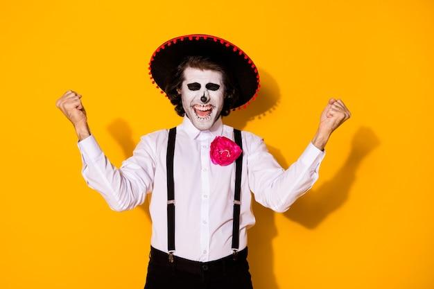 소름 끼치는 유령 갱스터 남자의 사진은 손 주먹을 들고 눈을 감고 성공적으로 라틴 지하 은행을 털고 흰 셔츠 죽음 의상 설탕 두개골 멜빵 고립 된 노란색 배경
