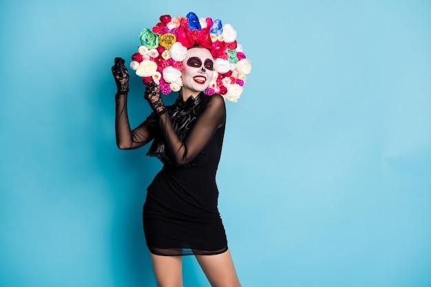 不気味なモンスターゾンビの女性の夢のようなダンスラテンバイブの写真は、マラカスがリズムを身に着けているふりをしています黒のショートミニドレス死の衣装バラのヘッドバンド孤立した青い色の背景