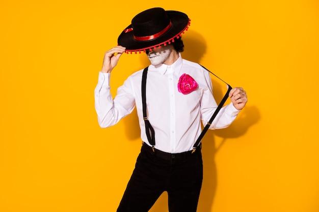 Фотография жуткого таинственного опасного парня, харизматического удерживающего кепку матадора, подготовить бой, большая бычья одежда, белая рубашка, костюм смерти розы, сахарный череп, сомбреро, подтяжки, изолированный желтый цвет фона