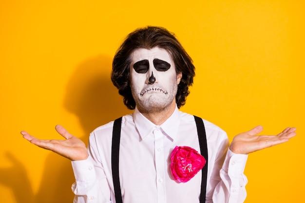 不気味な怖い悲しいアンデッドの生き物の写真剛毛の男が手を上げる泣く魂のギャンブルを失う取引をする悪魔が白いシャツを着るバラの死の衣装サスペンダー孤立した黄色の背景