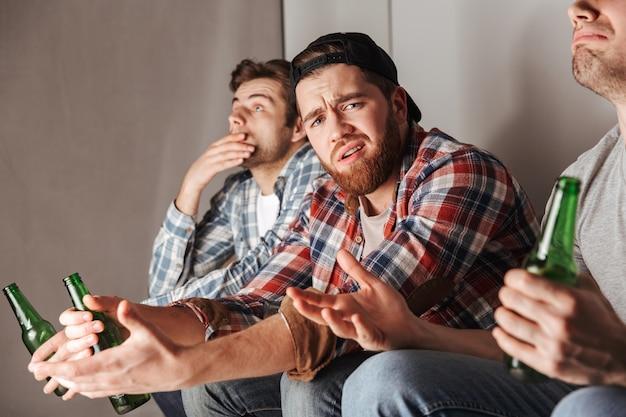 Фотография раздавленных парней, выражающих разочарование и неудовлетворенность во время просмотра футбольного матча в квартире с плохими результатами