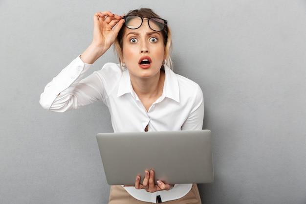 眼鏡をかけて立って、オフィスでラップトップを保持している好奇心旺盛なビジネスライクな女性の写真、孤立
