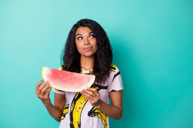 Фотография любопытной темнокожей девушки с пустым пространством, держащей кусочек арбуза, в розовой футболке, изолированной на фоне бирюзового цвета