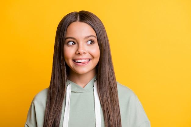 Фотография любопытной смешной детской девочки, одетой в повседневный зеленый наряд, показывает язык, глядя в пустое пространство, улыбаясь, изолированный желтый цвет фона