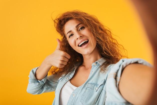 Фотография кудрявой привлекательной женщины, улыбающейся и показывающей большой палец вверх при съемке селфи, изолированной на желтом фоне