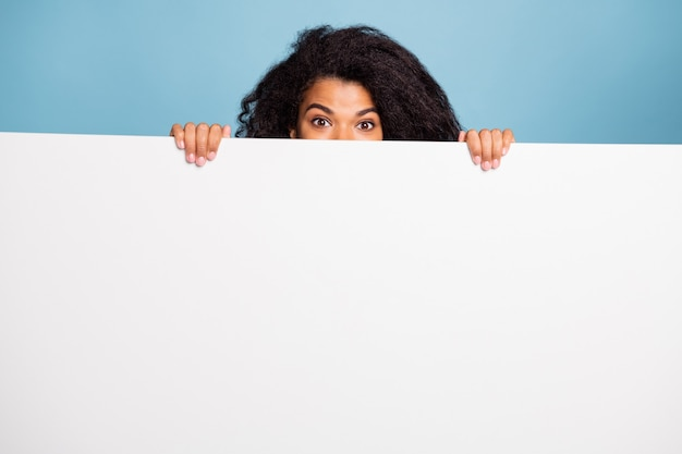 孤立したパステルブルーの色の背景を保持している後ろに隠れている白いバナーに関する情報を提示する巻き毛の波状のかわいい陽気なポジティブな茶色の髪の写真