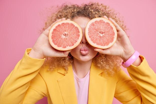 巻き毛の女性の写真はグレープフルーツのスライスで目を覆い、多くのビタミンを含む健康的な食べ物を食べ、ピンクの壁に隔離された腕に黄色のフォーマルな衣装のブレスレットを身に着けています。女性はエキゾチックな果物を持っています