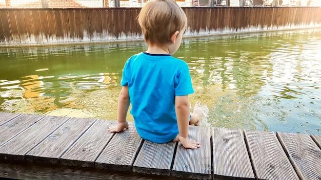 旧市街の運河の川岸に座って、足で水をはねかけるかわいい3歳の男の子の写真。
