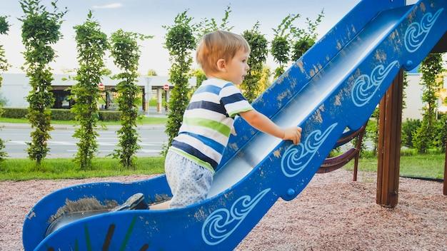 공원의 어린이 놀이터에서 큰 미끄럼틀을 타고 등반하는 귀여운 3살 소년의 사진