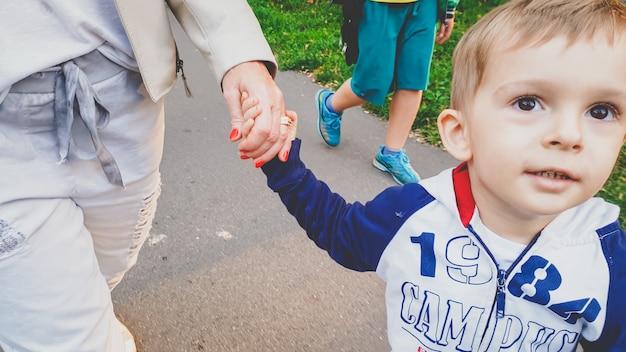 가을 공원에서 가족과 함께 걷고 있는 귀여운 3살 소년의 사진