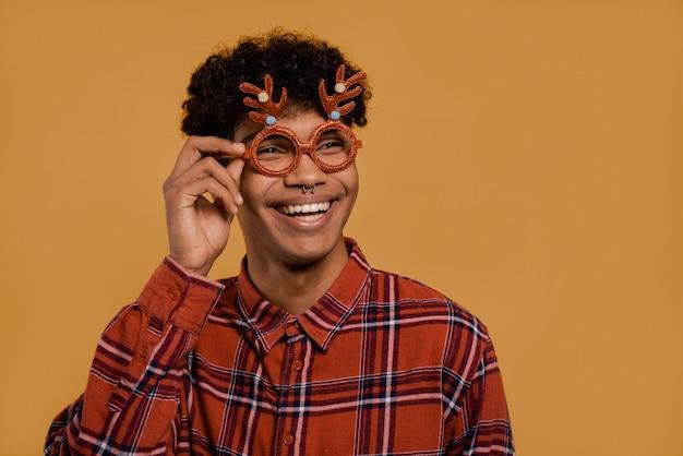 귀여운 아프리카 남성 농부의 사진은 크리스마스 안경과 미소를 착용합니다. 남자는 격자 무늬 셔츠, 고립 된 갈색 배경을 착용합니다.