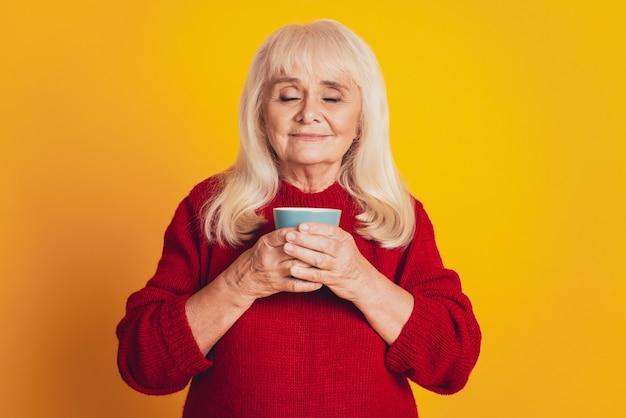 Фото милой пожилой женщины в возрасте, пьющей аромат какао на желтом фоне