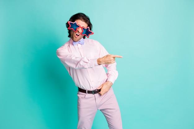 Фотография симпатичной брюнетки с волнистыми волосами, студентка, одетая в розовый наряд, танцует, указывая пальцем на пустое пространство, изолированный бирюзовый цвет фона