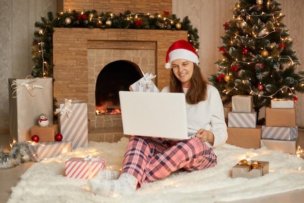 그녀의 노트북으로 새해 이브에 일하거나 누군가를 인사하기 위해 화상 통화를하는 귀여운 매력적인 매력적인 소녀의 사진, 체크 무늬 바지와 산타 모자를 쓰고 미소로 노트북 스크린을 본다.