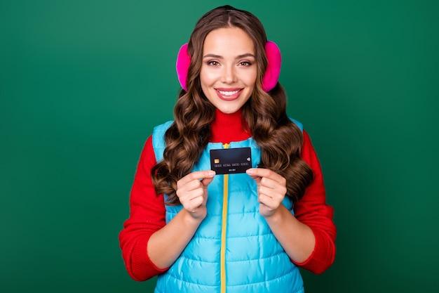 귀여운 매력적인 젊은 여성의 사진은 완벽한 선택 일반 고객 할인을 추천하는 신용 카드를 들고 분홍색 귀 보온기 파란색 조끼 빨간색 스웨터 격리 된 녹색 배경