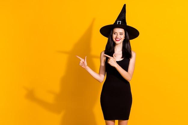 かわいい魅力的な若い魔術師の魔術師の女性の直接指の空のスペースの光沢のある笑顔の写真は、魔術を着用する黒い帽子の短いミニドレスを分離した明るい黄色の背景を提案します