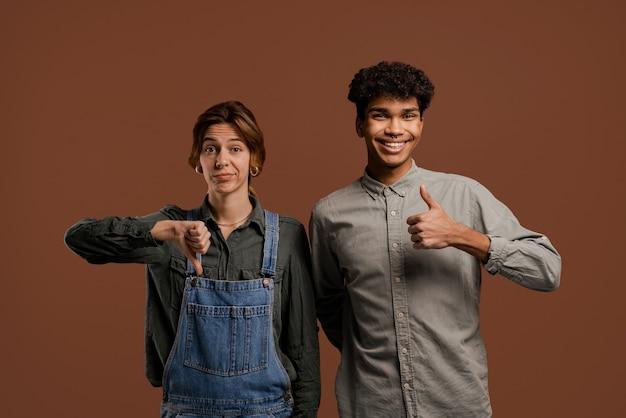 かわいいカップル農家の写真。女性の農民は親指を下に向けますが、男性は現れます。女性はデニムのオーバーオールを着用し、男性はtシャツ、孤立した茶色の背景を着用しています。