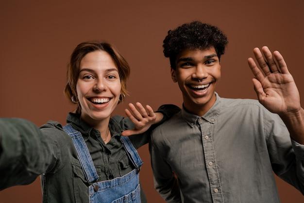 귀여운 커플 농부의 사진은 멋진 미소로 셀카를 찍습니다. 여자는 데님 바지를 입고, 남자는 티셔츠, 고립 된 갈색 배경을 착용합니다.