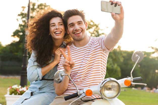 도시 공원에서 스쿠터에 함께 앉아있는 동안 휴대 전화에 셀카를 복용 귀여운 커플의 사진