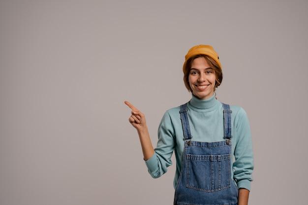 Фотография милых женских хипстерских улыбок и очков слева. белая женщина носит джинсовый комбинезон и шляпу изолировал серый цвет фона.