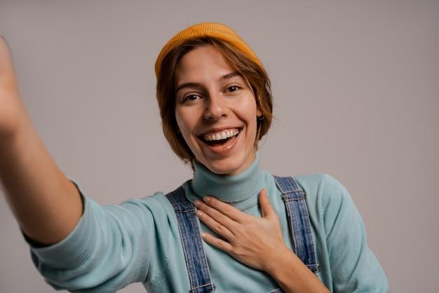 귀여운 여성 hipster의 사진은 셀카를 찍고 좋은 이빨로 미소 짓습니다. 백인 여자는 전체 데님을 착용하고 모자는 회색 배경에 고립.