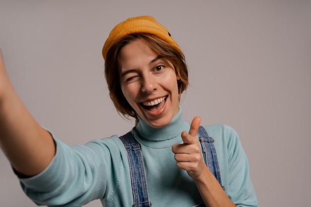 귀여운 여성 힙 스터의 사진은 셀카를 찍고 손가락을 스냅하고 좋은 이빨로 미소를 짓습니다. 백인 여자는 전체 데님을 착용하고 모자는 회색 배경에 고립.