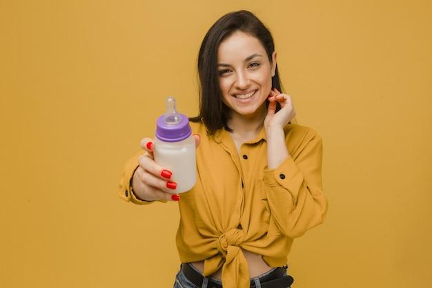 かわいい女性の写真はミルクの赤ちゃんのブートルを保持します