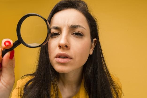 かわいい女性の写真は虫眼鏡を持って何かを探しています