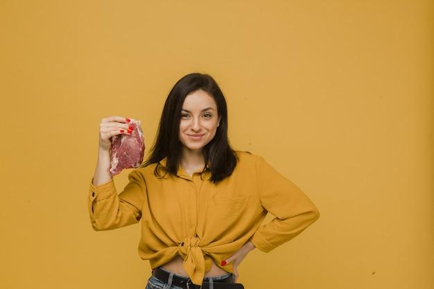 Фотография милой самки держит кусок мяса, вегетарианский образ жизни. носит желтую рубашку, изолированный желтый цвет фона.