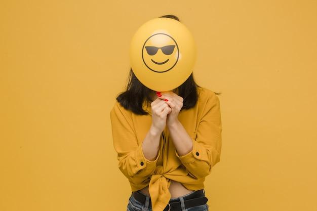Фотография симпатичной женщины держит желтый баллон с смайликами. носит желтую рубашку, изолированный желтый цвет фона.