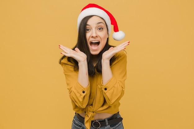 Фотография симпатичной девушки в новогодней шапке удивлена подаркам. носит желтую рубашку, изолированный желтый цвет фона.