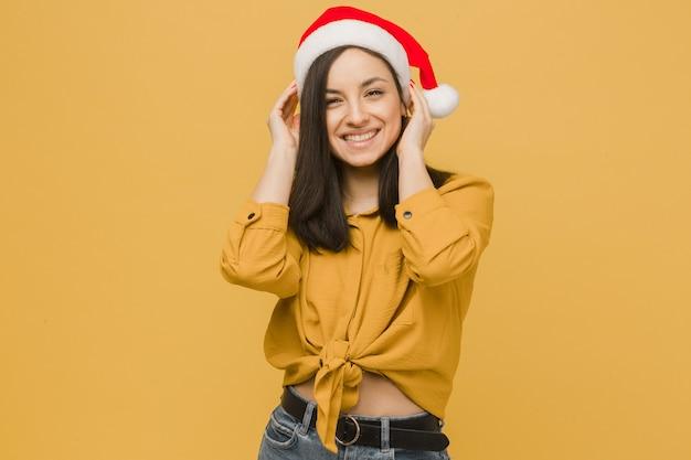 Фото милой девушки в новогодней шапке. носит желтую рубашку, изолированный желтый цвет фона.