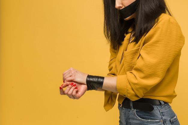 Фотография милой женщины-жертвы с заклеенным ртом, похищение. носит желтую рубашку, изолированный желтый цвет фона.