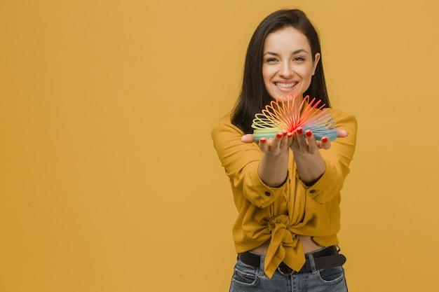Фотография симпатичной девушки с красивой улыбкой держит обтягивающую. носит желтую рубашку, изолированный желтый цвет фона.