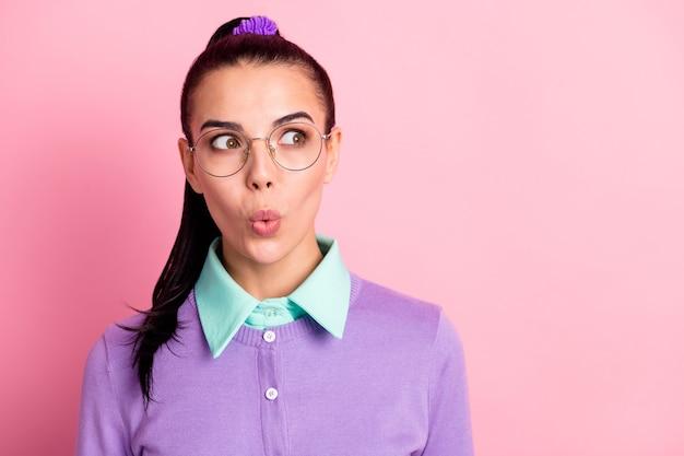 Фотография симпатичной девушки выглядит пустым пространством в шоке, губы в очках, фиолетовый кардиган, изолированный розовый цвет фона