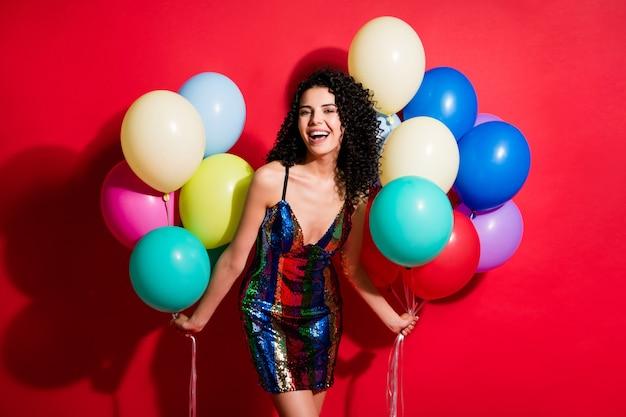 Фото симпатичной девушки двумя руками держат много воздушных шаров, одетых в глянцевое мини-платье, изолированное ярким красным цветом фона
