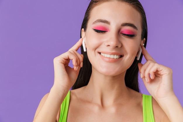 イヤポッドを使用して笑顔で明るいメイクでかわいい幸せな女性の写真